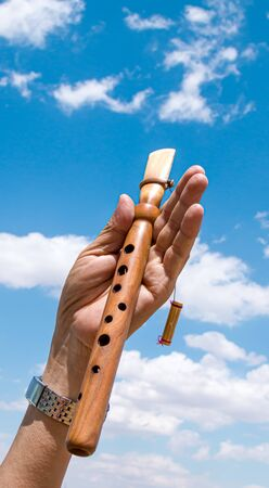 National musical instrument duduk in hand against the sky