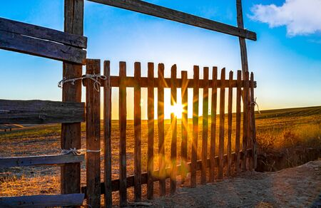 Old gate in the steppe on the background of the sunrise. Landscape. The day will be hot. 版權商用圖片