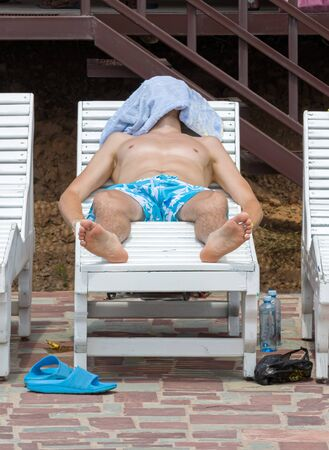 A man sleeps on a lounger near the pool. The concept of tourism and outdoor activities. Standard-Bild