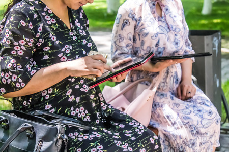 Shymkent, Kazakhstan - May 31, 2019; Women in the city park with a tablet. The concept of using modern gadgets in everyday life. Editorial