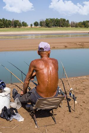 Elderly tanned fisherman by the river 版權商用圖片