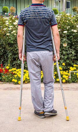 Man with crutches walks in the park. Standard-Bild