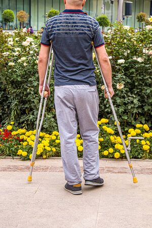 Man with crutches walks in the park. Stock Photo