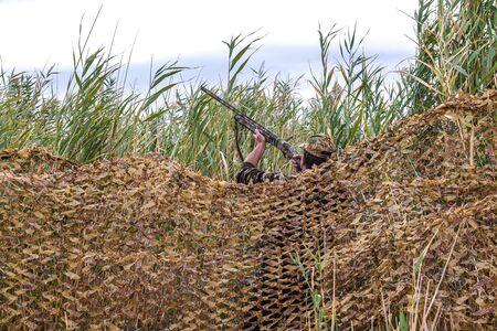 Reed camouflage net in nature. Ambush hunter