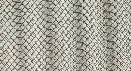 Wall of asbestos-cement sheet and metal mesh netting as background for design