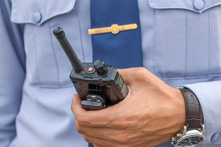 Intercom portable walkie-talkie in the hand of a policeman on the street close-up