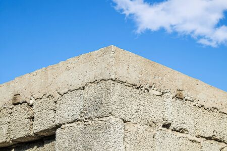 Brick cinder block wall as background for design on sky background 写真素材