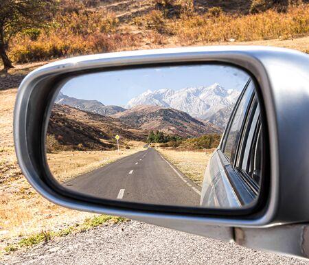 Mountain landscape in a car mirror
