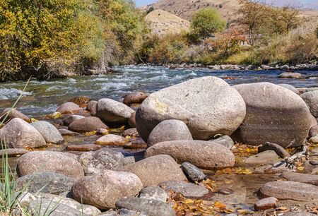 Stones in a mountain river landscape. Water in a stormy mountain river