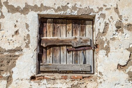 The old window on the old wall is boarded up by old boards. Selective focus Stock Photo