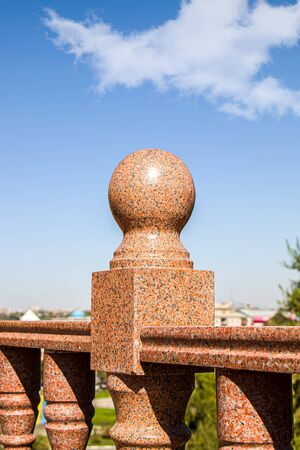 Close-up granite balustrade element against the sky
