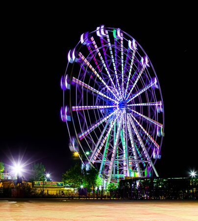 Blurred lights of a ferris wheel in a park.