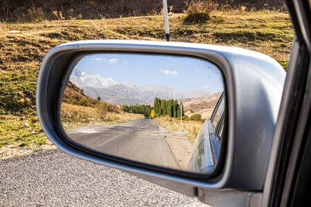 Mountain landscape in a car mirror