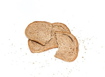 Sliced rye bread with crumbs on a white background. Selective focus.