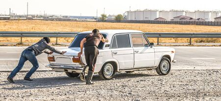 Young people push an old stalled car on the road 写真素材
