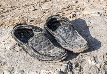 Old dusty shoes on the road in nature
