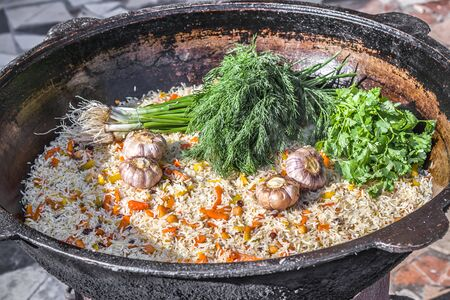 Close-up of national rice pilaf with spices and fresh herbs in a cauldron
