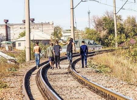 Young people teenagers walk on the railroad tracks