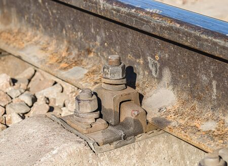 Fastenings of metal railway rails close-up 写真素材