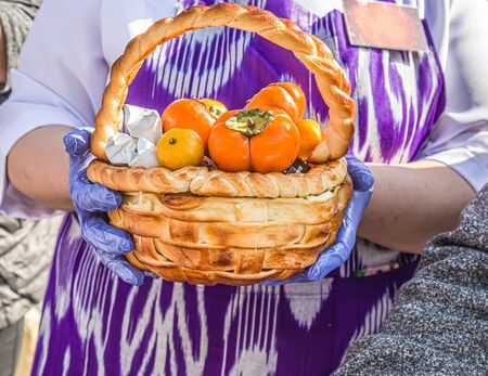 A basket baked from fancy pastry with fruits and sweets in it.
