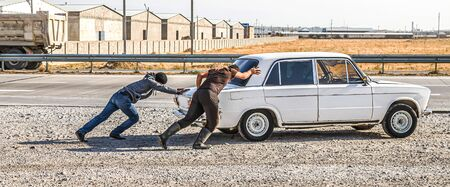 Young people push an old stalled car on the road Reklamní fotografie