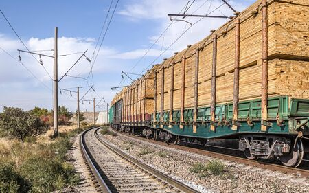 Railway transport carrying construction lumber