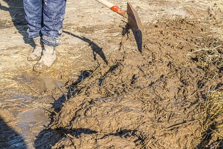 Mixing clay adobe with straw with a hand shovel. Banque d'images