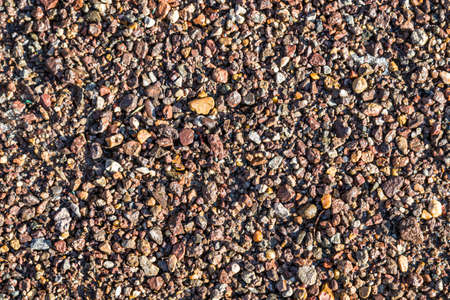 Small wet stones on the shore close-up as a background. Standard-Bild