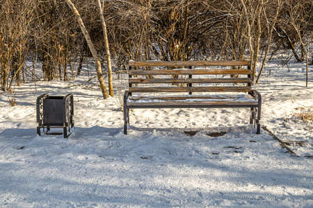 Bench in a city park. First snow. 写真素材