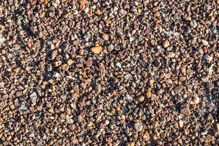 Small wet stones on the shore close-up as a background. 写真素材