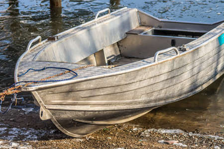 A metal boat on the shore of a freezing lake. Standard-Bild