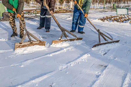 People clean the road from snow with hand tools.