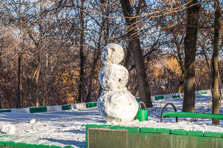 Snowman in a city park from the first snow