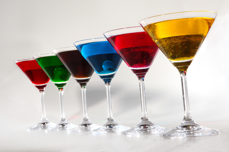 non alcoholic: Group of glasses with colored beverages on white background Stock Photo