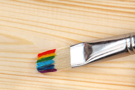 bristle: Paint brush with rainbow strokes on bristle on wooden background