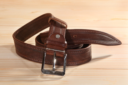 Leather belt with metal buckle on wooden background