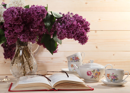 lilacs: Bouquet of lilacs, open book, spectacles, teapot and cup of tea on wooden background
