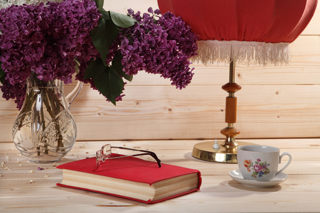 tea lamp: Bouquet of lilacs, book, spectacles, cup of tea and table lamp on wooden background Stock Photo
