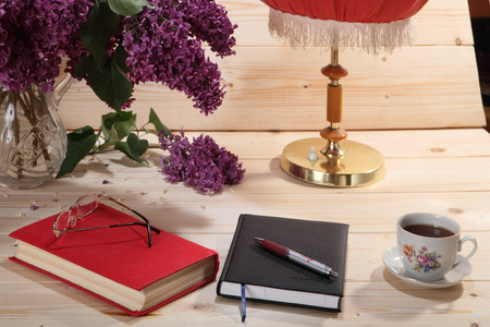 tea lamp: Bouquet of lilacs, book, notebook, spectacles, cup of tea and table lamp on wooden background