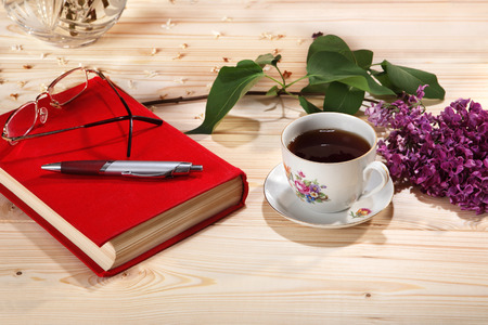 lilacs: Cup of tea, branch of lilacs, book, spectacles and pen on wooden background Stock Photo