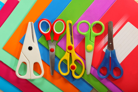 Scissors on background of colored school notebooks