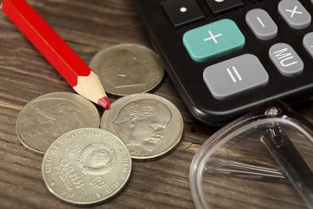 lenin: Calculator, red pencil, old coins of the USSR and glasses lie on a wooden table. Close-up. Selective focus