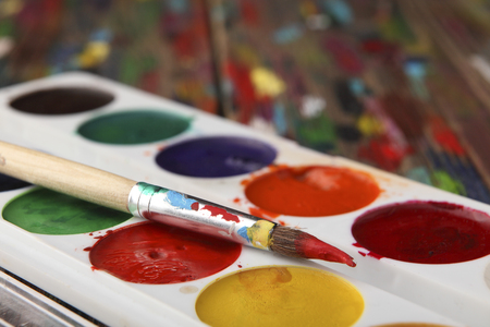 A brush dyed in red paint lies on a set of watercolor paints. Close-up. Sharpness on the tip of the brush