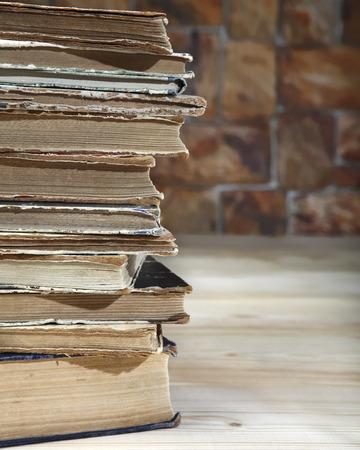 pegamento: El borde de una pila de viejos libros reclinados en una tabla de madera. De cerca Foto de archivo
