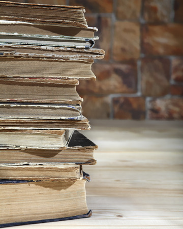 The edge of a stack of old books recumbent on a wooden table. Close-up Stock Photo