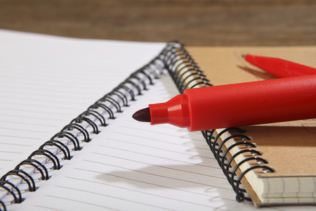 A red marker and a ballpoint pen lie on school notebooks. Close-up