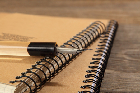 The old penholder with the pen lies on the notebooks sewn with metal springs on a wooden table. Retro stylized photo. Close-up