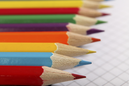 Color pencils lie hardly on the sheet of a school notebook. Selective focus Stock Photo