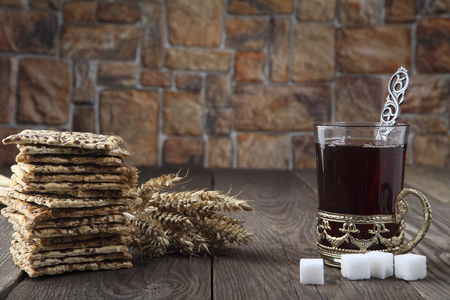 chasing: Still life with a cracker, black tea in a glass with a retro glass-holder, wheat spikes and pieces of sugar. Retro stylized photo. Close-up