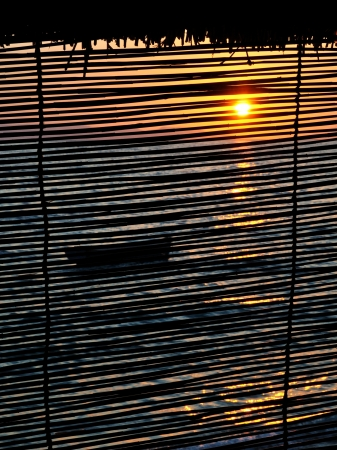 View of the boat on the sea at sunset across the blind Stock Photo